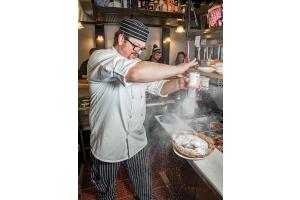 Chef Brian Little dusts powdered sugar onto his pannekoeken, or German pancake.